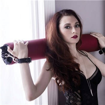 Liberator Talea Spreader Bar with bar behind womans head with wrist cuffs used
